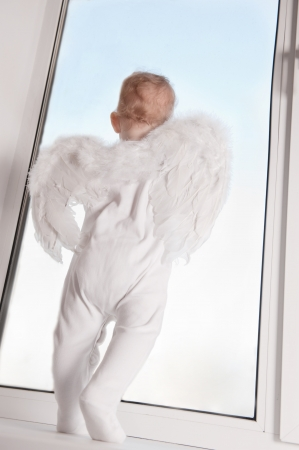 Cute baby with angel wings on windowsill photo