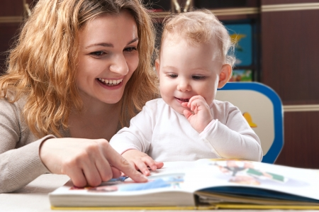 Young mother with her little daughter reading book photo