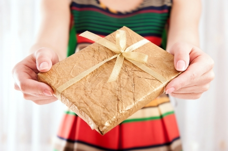 wrapped present: Young female holding a book wrapped in golden paper with ribbon bow