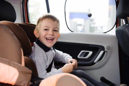 Happy child smiling in car seat photo