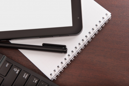 portable information device: Tablet computer with white screen and laptop, pen and paper notebook