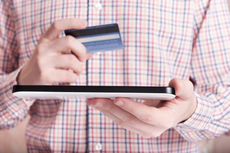 Young man shopping using credit card and tablet pc photo