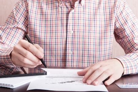 Young man analyze som document with pen in his hand and using tablet PC Stock Photo - 15894020