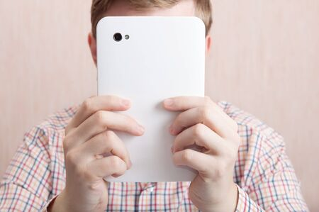 Man holding a digital tablet in front of his face.  photo
