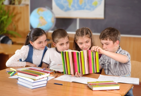 Four elementary aged pupils reading book in classroom photo