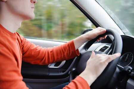 Young seriously man driving a car. Two hands on a steering wheel Stock Photo - 15894015