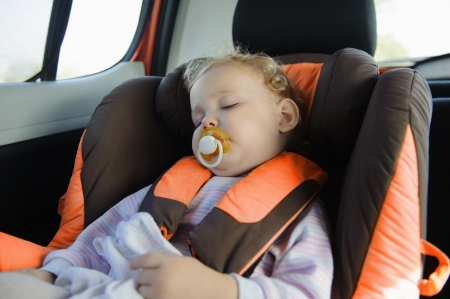 Cute blond baby sleeping peacefully in baby car seat photo
