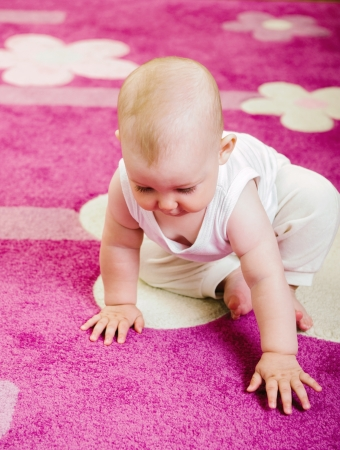 Cute baby crawling on soft pink carpet Stock Photo - 15894082