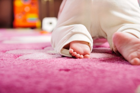 Cute baby crawling on pink carpet. Rear view. Primary focus on baby feet.
