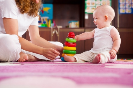 Cute baby playing with her mother on pink carpet Stock Photo - 15893999