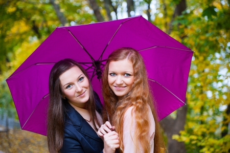 Two female friends standing under violet umbrella in autumn park photo
