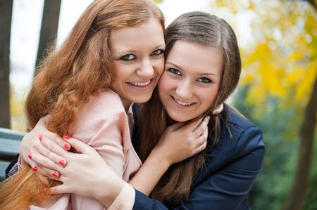 friends hugging: Two best friends embracing in autumn park Stock Photo