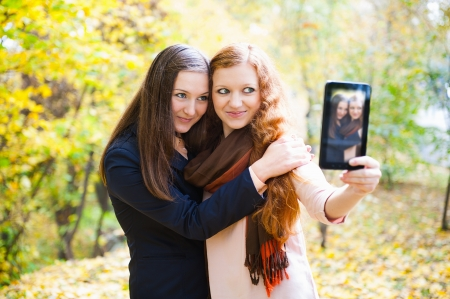 Two young girls taking picture via digital tablet pc in autumn park photo