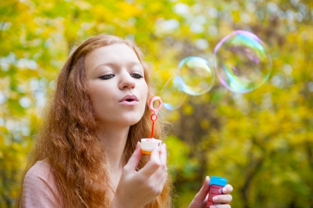 Young redhead girl blowing soap bubbles in autumn park photo