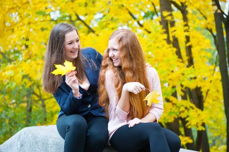 Two pretty girls sitting with yellow leaves in autumn park photo