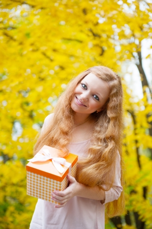 Attractive redhead girl with orange present box in autumn park photo