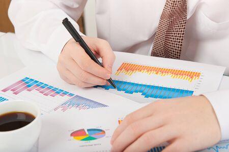 graph paper: Businessman in white shirt and necktie analysing graphs