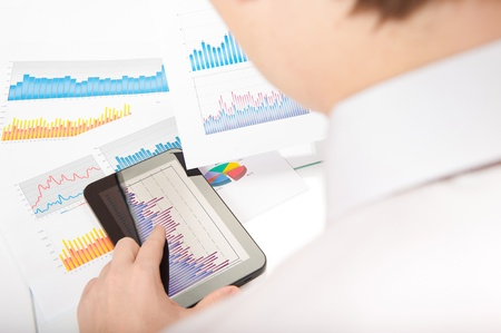 Businessman touching touchscreen digital tablet and analyzing financial chart photo