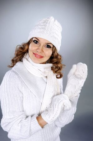 sweater girl: Beautiful young woman in white knitted sweater, scarf, hat and gloves