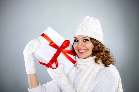 Beautiful young woman in knitted white clothes holding present box with red ribbon photo