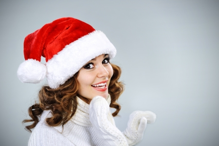 Beautiful young girl in Santa hat calling for New Years Eve photo