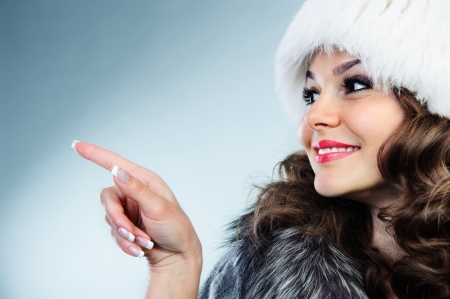 christmas manicure: Young woman in white fur hat in warm coat