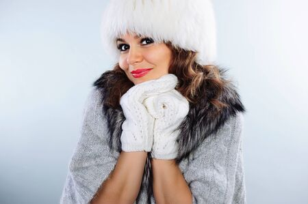 Beautiful young woman in white knitted gloves and fur hat photo
