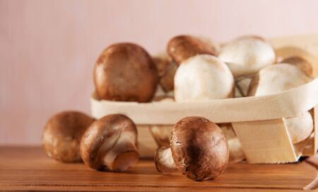 Brown and white champignon mushrooms in wooden basket photo