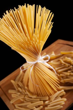 A bunch of long spaghetti pasta over dark background photo
