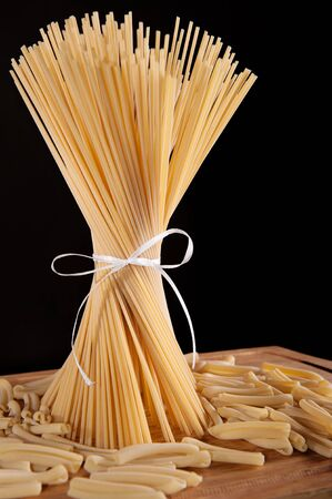 Ribbon tied bunch of spaghetti pasta over black background