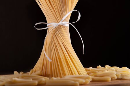 ribbon pasta: Ribbon tied bunch of spaghetti pasta over black background