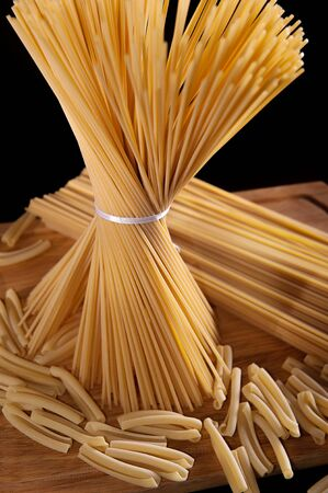 Ribbon tied bunch of spaghetti pasta over black background photo