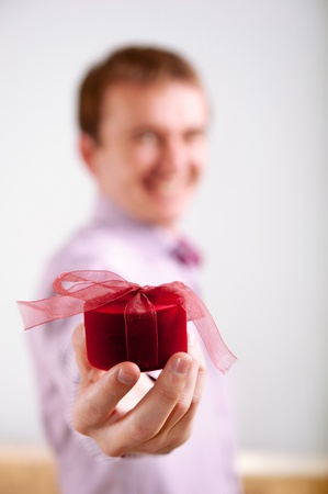 Man proposing by holding out a beautiful red ring box towards the camera. Selective focus on hands and ring box.  photo