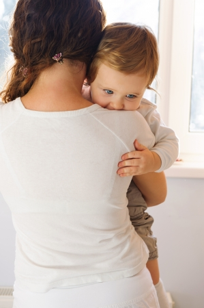 rear views: Mother holding her baby near window. Rear view. Stock Photo