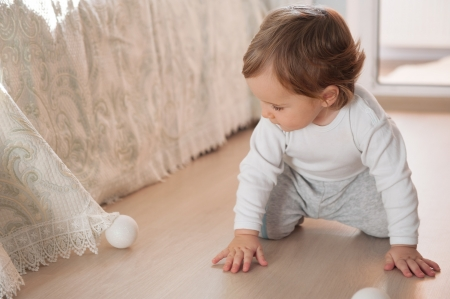 Little baby boy playing with silver Christmas balls on floor photo