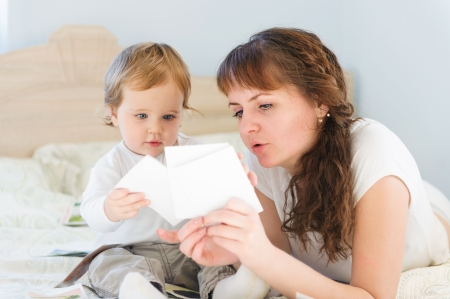 Cute boy with his mother playing with paper cards photo