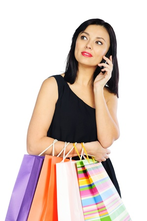 Young brunette woman with shopping bags talking via phone isolated on white background photo