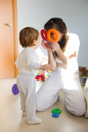 infant girl: Young mother and little son playing at home