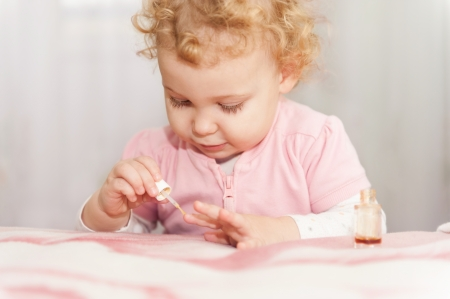Cute little baby playing with mothers manicure cosmetics photo