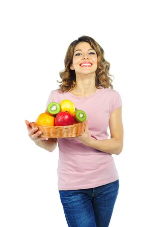 Beautiful young woman with basket of fruit  isolated on white photo