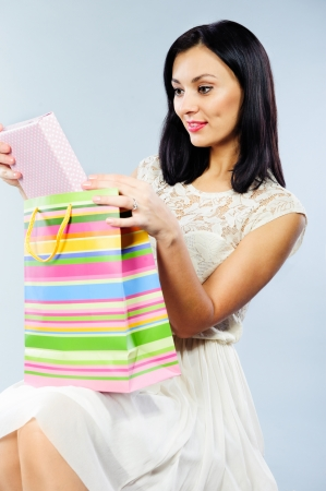 Beautiful young brunette taking out present from shopping bag photo