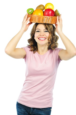 above head: Beautiful young girl holding basket with fresh fruits above her head. Isolated on white background Stock Photo