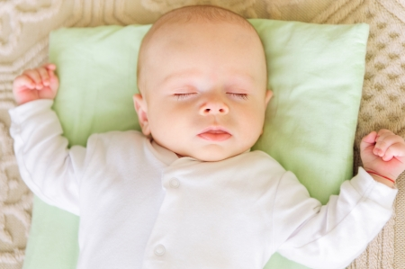 Cute newborn baby sleeping in bed on pillow Stock Photo - 17505780