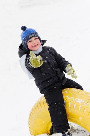 Little boy playing outdoors in snow. Showing thumb up photo