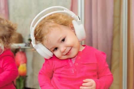 Lovely little girl is dancing in headphones photo
