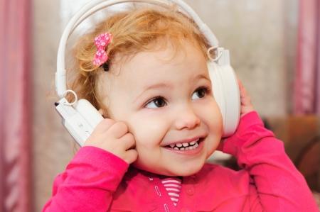 Cute little girl enjoying music using headphones photo