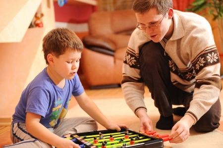 candid: Close-up of a little boy and his father playing board soccer game sitting on floor.