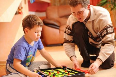 playroom: Primer plano de un ni�o peque�o y su padre tablero de juego juego de f�tbol sentado en el suelo.