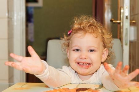 Sweet little girl with dirty facel eating cookie at home photo