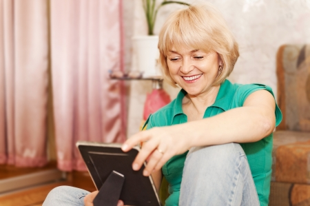 Portrait of mature woman looking at photo at home  photo